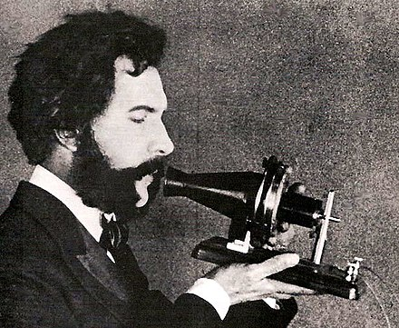 Actor portraying Alexander Graham Bell in a 1915 silent film. Shows Bell's first telephone transmitter (microphone), first displayed at the 1876 Centennial Exposition, Philadelphia. Actor portraying Alexander Graham Bell in an AT&T promotional film (1926).jpg