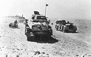 Armored vehicle convoy moving through a dessert