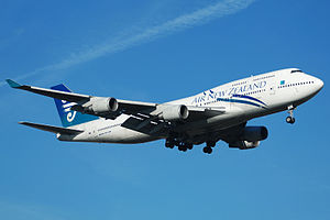An Air New Zealand 747-400 with its landing gear down and flaps down.  The aircraft is mostly white and blue aircraft and in-flight against a blue sky. On each of the two wings are two engines.