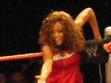 A curly haired woman stands on the apron of a wrestling ring with red ropes at the corner turnbuckle. The turnbuckle is black and has the red and white WWE logo on it. The woman is wearing a red dress with a whit trim across the top.