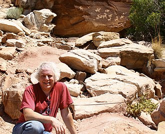 Kenneth Feder - Feder sits in front of historical petroglyphs showing Native Americans on horseback using bows and arrows to hunt bighorn sheep. The petroglyph panel is located in Arches National Monument in Moab, Utah.