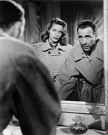 Lauren Bacall in black and white facing a mirror looking at Humphrey Bogart's reflection
