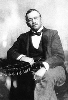 Black and white portrait of a seated man. He has a short beard, is wearing glasses and is dress formally