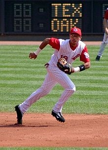A man in a white baseball uniform with red pinstripes and a red baseball cap running to his left