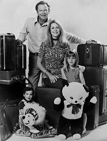 A black-and-white photograph of a man, a woman, a girl, and a boy, all looking at the viewer while surrounded by a large number of suitcases and two stuffed toys