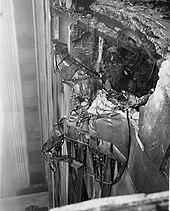 Черно-белое фото обломков самолета, врезанных в фасад, высоко