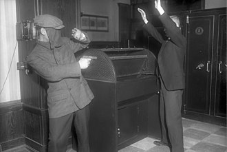 Robbery - A masked robber threatens a person with a gun in Germany, December 1931.