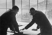 Photo noir et blanc. Adolf Hitler (à droite) et Albert Speer (à gauche), tous deux de profil, en costume sombre, discutent, la tête penchée au-dessus d'une carte étalée sur une plan. En arrière-plan, on voit, à travers une baie vitrée, un paysage de montagne.