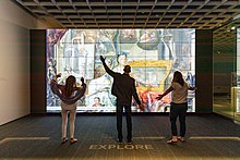 Three museum visitors strike different poses as they interact with a digital ARTLENS display.