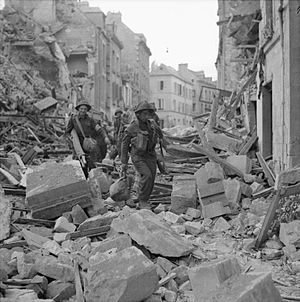 Operation Charnwood - British troops of I Corps pick their way through the rubble of Caen.