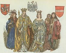 An elderly man wearing a crown, with a crowned woman on his left, surrounded by two young men and two young women