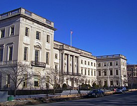 A three-story stone building, seen from its left, with two projecting wings and a balustrade running along the top. An American flag flies from a flagpole above the main entrance at the center, where a row of four columns marks the main entrance. There is an iron fence in front and small iron balconies on the wings.