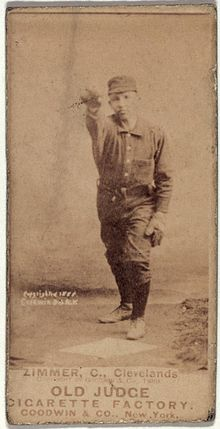 A sepia-toned baseball card image of a man wearing a dark-colored old-style baseball uniform and cap with his right arm raised in the air