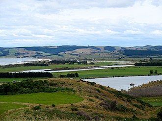 Kaitangata, New Zealand - A view of the Clutha River where it enters the sea from Kaitangata. Inch Clutha in the middle distance.
