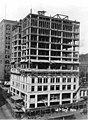 Construction of the William Rust building showing workers standing on top floor, completed wooden structural support, Tacoma (WASTATE 3388).jpeg