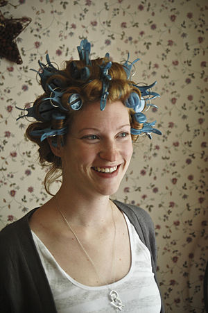 Smiling red haird woman with curlers in her hair.