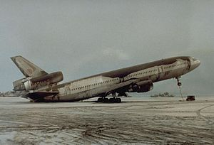 Volcanic ash - Volcanic ash deposits on a parked McDonnell-Douglas DC-10-30 during the 1991 eruption of Mount Pinatubo, causing the aircraft to rest on its tail. While falling ash behaves in a similar manner to snow, the sheer weight of deposits can cause serious damage to buildings and vehicles.