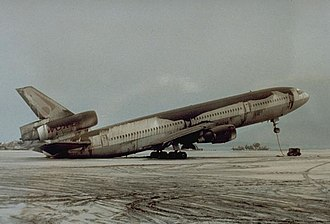 Volcanic ash - Volcanic ash deposits on a parked McDonnell-Douglas DC-10-30 during the 1991 eruption of Mount Pinatubo, causing the aircraft to rest on its tail. While falling ash behaves in a similar manner to snow, the sheer weight of deposits can cause serious damage to buildings and vehicles, as seen here, where the deposits were able to cause the 120 ton airliner's centre of gravity to shift.