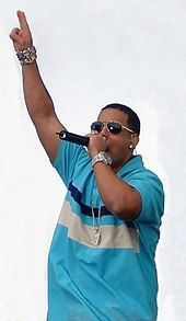 A man with sunglasses and a blue shirt holding a microphone.