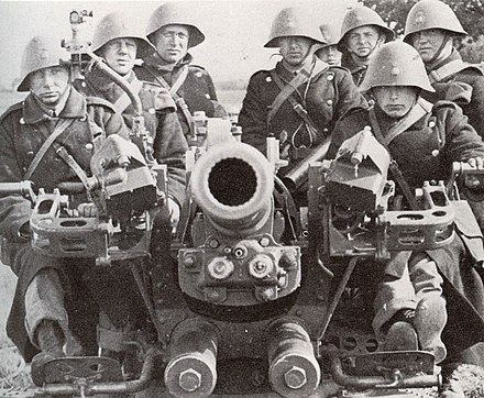 Danish soldiers man an anti-aircraft gun, 1940. All wear the distinctive Danish helmet. Danish anti-aircraft crew.jpg