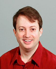 David Mitchell wearing a red shirt looks at the camera