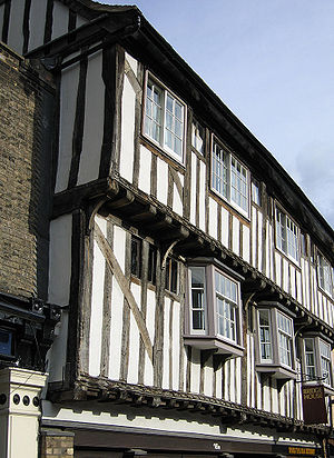 Jettying - A double jettied timber-framed building. The ends of the multiple cantilevered joists supporting the upper floors can easily be seen.