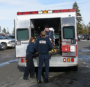 Emergency medical technician - EMTs loading an injured skier into an ambulance.
