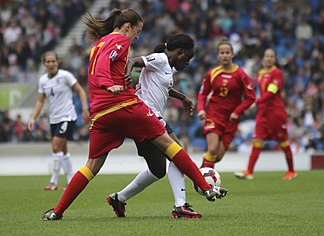 Eniola Aluko of England (in white) and Jovana Mrkić (in red) of Montenegro, 2014