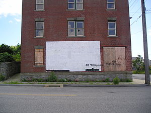 "Kelo v. City of New London - The same house, June 10, 2007. The ""thank you"" is still visible, but some windows are broken and others are boarded up, and ""No Trespassing"" has been spray-painted on it, as well as the URLs being obscured by spray paint."