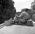 Fotograaf Willem van de Poll met een geweer op de boeg van een korjaal op de Cop, Bestanddeelnr 252-5654.jpg