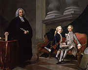 Conversation piece in oils: man dressed in black with a clerical collar stands beside two boys sitting on a settee, one wearing a grey suit the other a blue one. The man holds a sheet of paper; the boys hold a book.