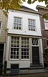 foto van Huis onder met rode pannen belegd schilddak en met lijstgevel waarin beneden zesdelige schuiframen, boven ramen met kleine roedenverdeling