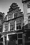 foto van Pand met trapgevel in haarlemse trant, natuurstenen geblokte bogen boven de ramen en horizontale banden, console met leeuwenkop onder middenpinakel Uitgebrand op 19 april 2014