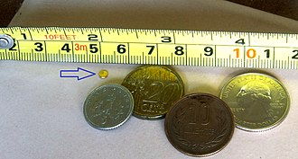 Grain (unit) - The small golden disk close to the 5 cm marker is a piece of pure gold weighing one troy grain. Shown for comparison is a tape measure and coins of major world currencies.