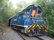 Diesel shunting locomotive in blue livery, displaced at an angle across the railway tracks, with damage visible at the rear