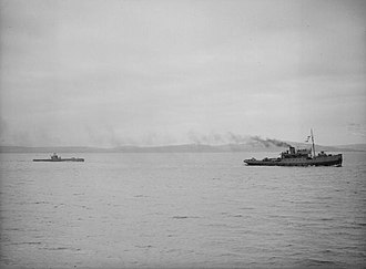 HMS Stubborn (P238) - HMS Stubborn being towed by a tug off Greenock, after being damaged by depth charges