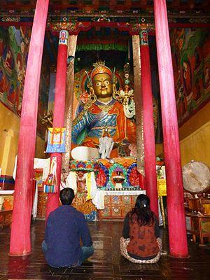 Hemis Monastery - Statue of Guru Rinpoche (Padmasambhava) and pilgrims at Hemis