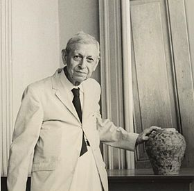 Henry Otley Beyer, standing with hand on ceramic pot.jpg
