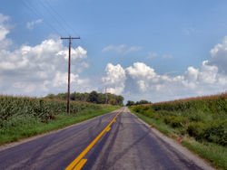 A typical rural county road in Indiana, USA, where traffic drives on the right. The yellow lines indicate that passing is allowed in the ongoing direction but not in the oncoming direction.