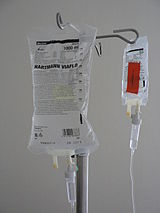 Photograph of two intravenous solution bags hanging from a pole.