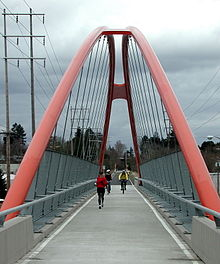 Two bicyclists and a jogger cross a long pedestrian bridge. The bright orange supporting arches of the bridge meet in the air about 30 feet (9 meters) above the bridge deck. Beyond the far end of the bridge is a paved bike path that continues into a woods in the distance.