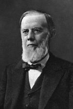 A black and white photographic portrait of a bearded Edwin Maxwell in his later years.