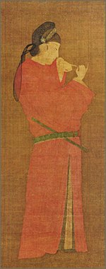 Portrait of a woman in disguise of a man wearing a red round-necked robe of the nobility and a cap of black gauze. A yokobue transverse flute is tucked in her obi and she is watchpg=PA159ing the fingers of both of her hands.