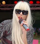 A woman with long blond hair and black sunglasses holding a microphone up to her mouth