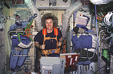 A woman running on a treadmill, anchored by orange straps. The wall behind her has a variety of items including clothing, ventilation hoses and instrument panels affixed to it.