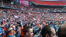 A three-tiered football stadium stand, the bottom two full of people clad mostly in white and orange. Several white and orange flags are visible.