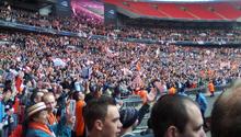 Трехъярусная трибуна футбольного стадиона, два нижних этажа заполнена людьми, одетыми в основном в белое и оранжевое.  Видны несколько белых и оранжевых флагов.