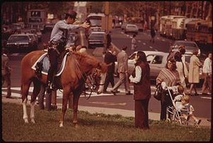 MOUNTED POLICEMAN ON BUSY DOWNTOWN THOROUGHFAR...