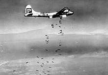Black and white photograph of a World War II-era bomber releasing bombs. The bombs are falling in a scattered pattern.