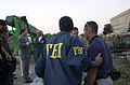 Members of the Federal Bureau of Investigation (FBI) meet outside the Pentagon Building hours after American Airlines Fight 77 was piloted by terrorists into the building, during the September 11, 2001 attacks 010911-N-AV833-025.jpg